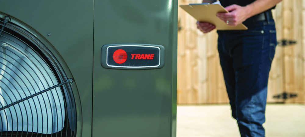 Chaffee Air tech inspecting heating installation of new Trane unit